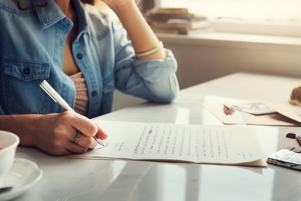 Frau schreibt einen lange Brift mit einem Kugelschreiber.