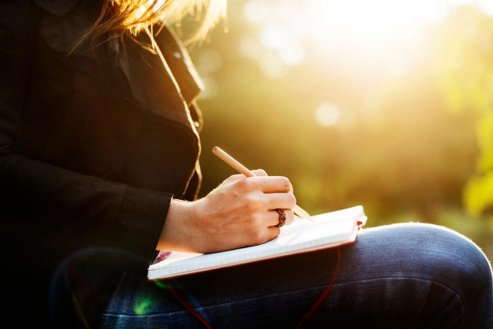 Die eigene Handschrift übern. Frau schreibt bei schönem Sonnenlicht mit einem Stift in ein Buch.