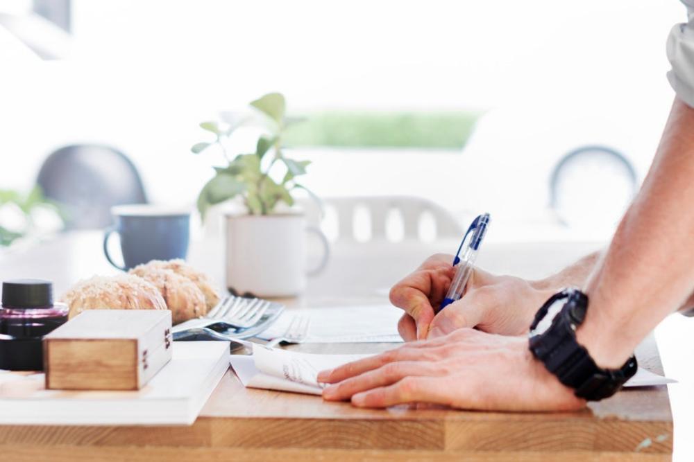 Mann schreibt mit einem Kugelschreiber auf ein Papier.